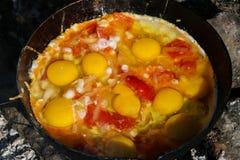 L'oeuf brouillé a fait frire sur des charbons dans la casserole sur le feu ouvert, cuisinier au-dessus d'un feu ouvert Images libres de droits