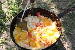 L'oeuf brouillé a fait frire sur des charbons dans la casserole sur le feu ouvert, cuisinier au-dessus d'un feu ouvert Photo libre de droits