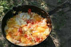 L'oeuf brouillé a fait frire sur des charbons dans la casserole sur le feu ouvert, cuisinier au-dessus d'un feu ouvert Image libre de droits