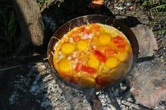 L'oeuf brouillé a fait frire sur des charbons dans la casserole sur le feu ouvert, cuisinier au-dessus d'un feu ouvert Photographie stock libre de droits