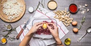 L'oeuf femelle de main se casse avec de la viande hachée sur la table de cuisine rustique, autour des ingrédients de mensonge pou Images stock