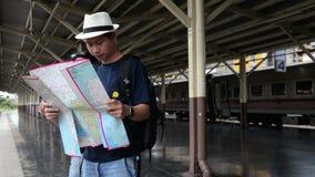 L'offensore ruba una borsa da uno sguardo turistico dell'uomo asiatico alla mappa