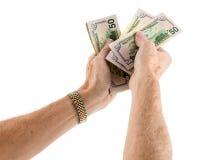 L'offerta caucasica delle mani di etnia incassa le banconote in dollari degli Stati Uniti cinquanta Fotografie Stock