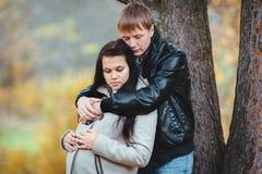 L'offerta del marito abbraccia la sua moglie incinta Fotografia Stock
