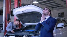 L'officina riparazioni dell'automobile, maschio triste del cliente si è rovesciata circa l'auto rotta con il cappuccio aperto che video d archivio