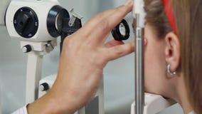 L'oftalmologo dell'uomo sta guardando in una lampada a fessura ed in una lente sull'occhio del paziente femminile archivi video