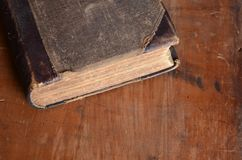 L'oggetto d'antiquariato ha stracciato il libro rilegato di cuoio che mette su un vecchio legno rustico fotografia stock libera da diritti