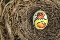 L'oiseau de poulet peint sur un oeuf de pâques placé dans les oiseaux nichent photos stock
