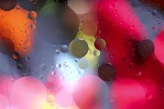 L'olio cade in acqua su un fondo colorato Fondo luminoso con i cerchi rosa grigi, di rosa, arancio e luminosi delle dimensioni di immagine stock