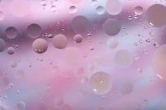 L'olio cade in acqua su un fondo colorato Superficie con il rosa ed i cerchi blu-chiaro delle dimensioni differenti fotografie stock
