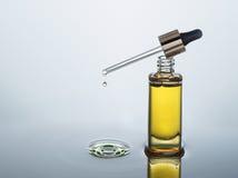 L'olio cosmetico d'idratazione sta sui precedenti scuri dell'acqua con spruzzata Immagini Stock