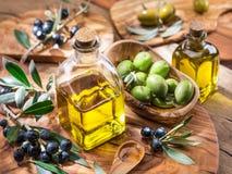 L'olio d'oliva e le bacche sono sul vassoio di legno verde oliva immagini stock