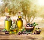 L'olio d'oliva e le bacche sono sulla tavola di legno Immagine Stock