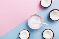 L'olio di cocco con le noci di cocco fresche fruttifica sulla vista superiore del fondo pastello minimo Cosmetico naturale ed org fotografia stock libera da diritti