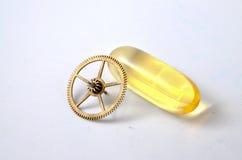 L'olio di fegato di merluzzo Omega 3 capsule di gel ed orologi spinge su fondo bianco Fotografia Stock