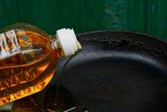L'olio di girasole è versato dalla bottiglia su una padella nera Fotografia Stock