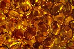 L'olio di pesce delle capsule di Omega 3, acidi si chiude su per un fondo fotografia stock