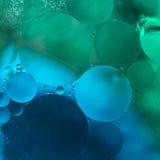L'olio verde e blu di pendenza cade nell'acqua - fondo astratto fotografia stock