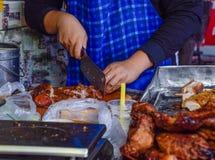 l'Oman che affetta carne di maiale per vendita nel mercato fotografie stock libere da diritti