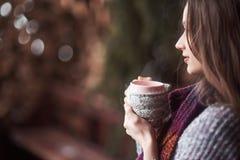 L'Oman portant le knit chaud vêtx la tasse de boissons de thé ou de café chaud dehors Photo stock