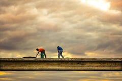 L'ombra dei lavoratori sta lavorando al punto del passaggio con il cielo nel tono drammatico Fotografia Stock