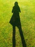 L'ombra della donna sull'erba verde fotografie stock libere da diritti