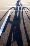 L'ombra di un ciclista sulla direzione della freccia della pavimentazione Fotografia Stock