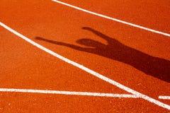 L'ombre de l'homme sur la voie courante rouge Image stock