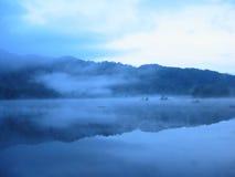 L'ombre de la côte sur la surface de lac Image libre de droits