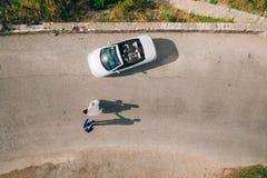 L'ombre des nouveaux mariés sur l'asphalte près de la yole de mariage photos stock
