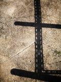 L'ombre du bâtiment à pans de bois en acier encoché d'angle sur les cailloux sales cimentent le plancher photos libres de droits