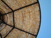 L'ombrello di sole di vimini sui precedenti del cielo blu dettaglio immagini stock