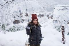 L'ombrello trasparente di condizione e della tenuta della donna nell'inverno e nella neve sta cadendo con fondo della campagna in fotografia stock libera da diritti