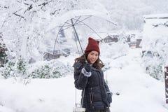 L'ombrello trasparente di condizione e della tenuta della donna nell'inverno e nella neve sta cadendo con fondo del villaggio inn fotografie stock