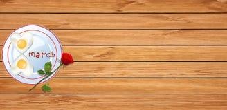 L'omelette avec le ketchup marque avec des lettres la rose du 8 mars et du rouge sur le dos en bois Images stock