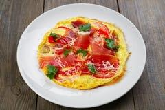 L'omelette avec le prosciutto et les tomates, se ferment  photo stock