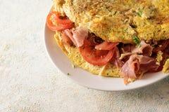 L'omelette végétale a rempli de tomates, de jambon de prosciutto et de pairs image stock