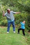 L'oncle enseigne le neveu à sauter des pierres Images libres de droits