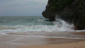 L'onda del mare ha colpito le rocce sulla spiaggia sabbiosa video d archivio