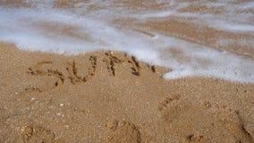 L'onda del mare lava la parola via scritta dell'estate stock footage
