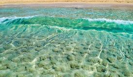 L'onda del mare si muove verso la riva che prende la sabbia dal fondo di Fotografie Stock