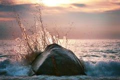 L'onde impressionnante avec éclabousse au coucher du soleil Photo stock