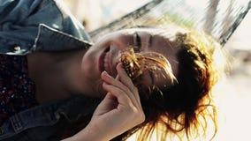 L'ondeggiamento felice della ragazza in amaca sulla spiaggia sorride in camera Giorno pieno di sole Capelli di scossa video d archivio