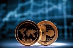 L'ondulazione dorata del xrp due conia con i grafici finanziari su fondo immagini stock