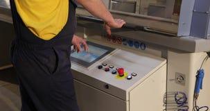 L'opérateur actionne une ligne automatisée, les travaux d'opérateur près d'un moniteur moderne de machine, contrôle automatisé, clips vidéos