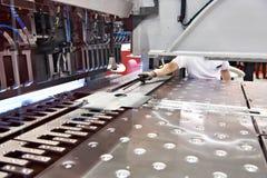 L'opérateur de la machine place l'objet dans le fléchisseur automatique de panneau images stock