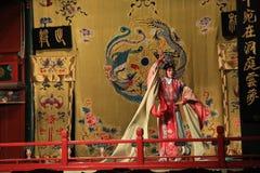 L'opera di Pechino, sulla fase un guerriero femminile balla in un vestito tradizionale luminoso Fotografia Stock