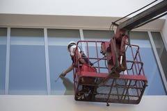 L'operaio è finestre di pulizia Immagini Stock Libere da Diritti