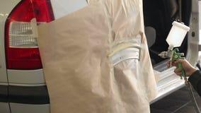 L'operaio che vernicia un'automobile parte in una cabina della vernice archivi video