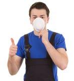 L'operaio con una mascherina e pollici aumenta il segno Immagini Stock